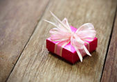 Gift box on old wood table — Stock Photo