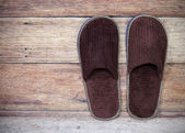 Brown home slippers on wood floor — Stock Photo