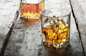 Faceted glass of whiskey with ice and a decanter — Stock Photo