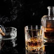 Glass of whiskey with ice, and a carafe of steaming cigar — Stock Photo #62336925