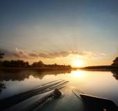 Beautiful dawn morning in an inflatable boat with a paddle — Stock Photo
