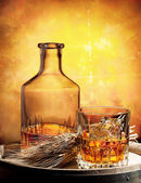 Glass of whiskey decanter and ears of wheat — Stock Photo
