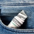 Rolled straw hundred-dollar bills in your pocket jeans — Stock Photo #67922233