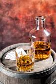 Faceted glass and dusty decanter of brandy and cards — Stock Photo