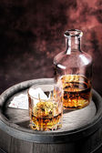 Faceted glass and dusty decanter of brandy — Stock Photo