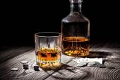 Glass and bottle of whiskey and playing cards and money — Stock Photo