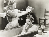 Maid squeezing sponge on woman in bathtub — Foto Stock