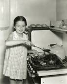 Young girl pours gravy over roast — Stock Photo