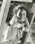 Little girl leaning on ladder — Stock Photo