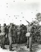 Soldiers shooting at enemy parachuting into field — Foto Stock