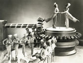 Chorus girls dancing on machine part — Foto Stock