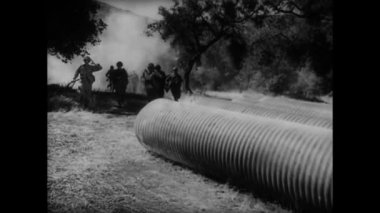 Soldiers running into large tubes — Stock Video