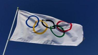 Bandera olímpica ondeando en el cielo azul brillante — Vídeo de Stock