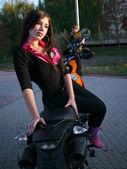 Schöne junge brünette auf einem motorrad. — Stockfoto