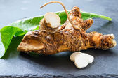 Roots and leaves of horseradish on a slate board — Stock Photo
