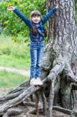 Little cheerful girl teetering on the roots of a tree — Stock Photo