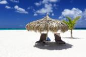 Beach umbrella with loungers on the tropical island — Stock Photo