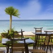 Table and chairs in outdoor restaurant on tropical beach — Stock Photo #55273387