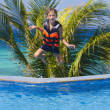 Young happy boy jumping in swimming pool on tropical background — Stock Photo #55274687