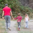 Father and two children boy and girl walking on natural backgrou — Stock Photo #55274829