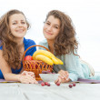 Two young happy women enjoying life during outdoor picnic with f — Stock Photo #55275819