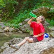 Young happy smiling child boy drinking water on forest river bac — Stock Photo #55276189