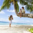 Three children - boy and girls - sitting on palm tree on tropica — Stock Photo #55276901