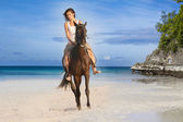 Young beautiful woman riding a horse on tropical beach — Stock Photo