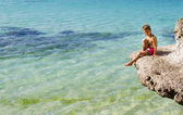Young happy child boy sitting on rocks on tropical sea backgroun — Stock Photo
