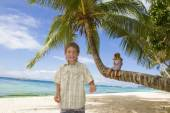 Two young happy kids - boy and girl - on tropical beach backgrou — Stock Photo