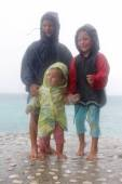 Three happy children - boy and girls - under rain on storm sea b — Stock Photo