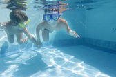 Two children diving in masks underwater in pool — Stock Photo