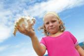 Cute smiling child girl with big sea shell — Stock Photo