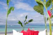 Table set for meal on tropical beach — Stock Photo