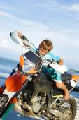 Outdoor portrait of young happy smiling boy riding motorbike on  — Stock Photo