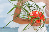 Beautiful bride holding bridal bouquet on natural background — Stock Photo