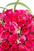 Wedding rings and bridal bouquet of pink roses isolated over whi — Stock Photo