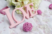 Word love and decoration details over white, wedding decor — Stock Photo