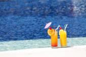 Two glasses of fruit juice on blue water background — Zdjęcie stockowe