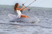 Young beautiful woman in wedding dress kitesurfing on water back — Photo