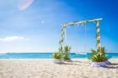 свадебное колебание, украшенное цветами на тропическом пляже песка — Стоковое фото