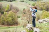 Young child boy looking through binocular to the country side — Stock Photo