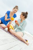 Two young happy women enjoying life during outdoor picnic with f — Stock Photo