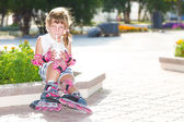 Cute happy child girl roller skating on natural background — Fotografia Stock