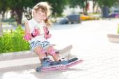 Cute happy child girl roller skating on natural background — Stockfoto