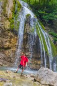 Young happy smiling child boy on waterfall background — Stock Photo