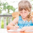 Young child girl writing in notebook, outdoors portrait, educati — Stock Photo #57501537