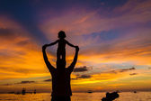Silhouettes of father and child on sunset sea background — Stock Photo