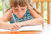 Young child girl writing in notebook, outdoors portrait, educati — Stock Photo