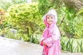 Young child girl in raincoat under rain drops, outdoor portrait — Stock Photo
